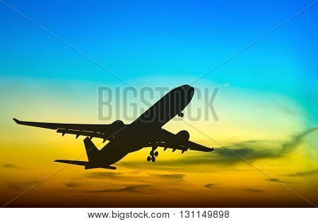 Silhouetted commercial airplane flying at beautiful sunset