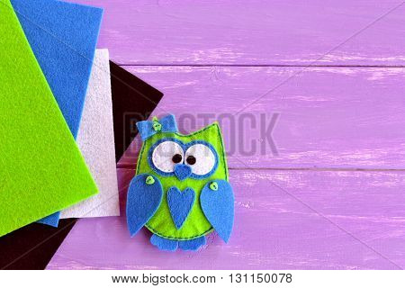 Owl felt sewing pattern. Kids' needlecrafts. Stuffed toy sewing bird. Bird toy you can make at home. Felt sheets. Wooden background with empty place for text
