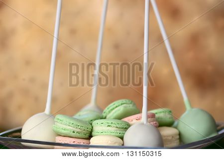 Delicious colorful green light pink sweet french macaroons and cake pops on sticks laying on plate on blur background