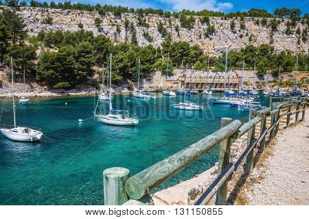 Narrow fjords between stony coast. White sailing yachts wait for the owners.  National Park Calanques on the Mediterranean coast