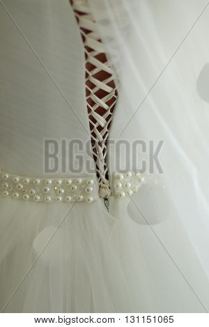 Back of beautiful elegant wedding white dress with lacing corset and belt beaded by pearls