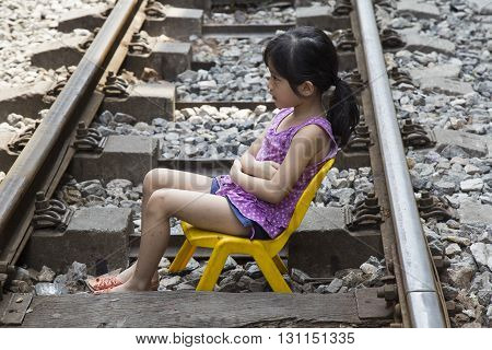 Hanoi, Vietnam - May 21, 2016: Close up of a Vietnamese little girl sitting right on the railroad and houses on the railway track. It's dangerous to live here but people don't have many choices.