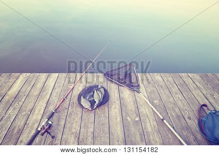 Retro Toned Fishing Equipment On A Wooden Pier.