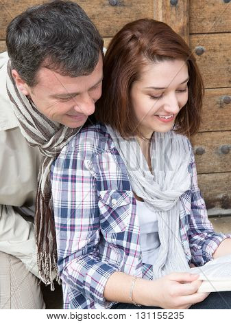 Smiling Couple Sitting On Bench Looking At Guide Of Tourism