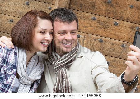 Smiling Couple In A Park Sitting In A Bench Doing Selfie