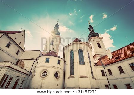 The Basilica of the Assumption of Our Lady in Strahov Monastery, Prague, Czech Republic. Sun shining on blue sky. Vintage