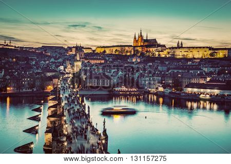 Charles Bridge on Vltava river in Prague, Czech Republic at late sunset, night. View on Prague Castle, Hradcany. Vintage