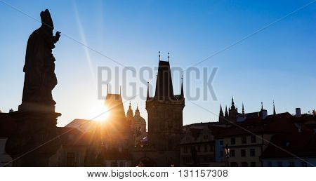 Charles Bridge at sunrise, Prague, Czech Republic. Dramatic statues and medieval towers. Silhouette photography style