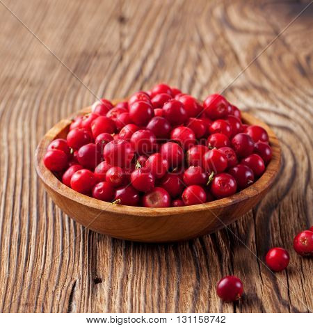 Cowberries, red bilberries, cranberries in a rustik bowl on a wooden background
