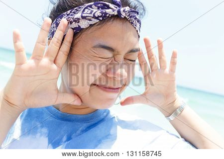 Young asian woman blue and white shirt stand at beach and open both hands at face