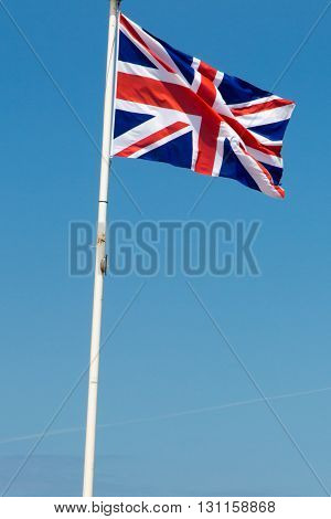 British Flag Blowing In The Wind Under Blue Sky