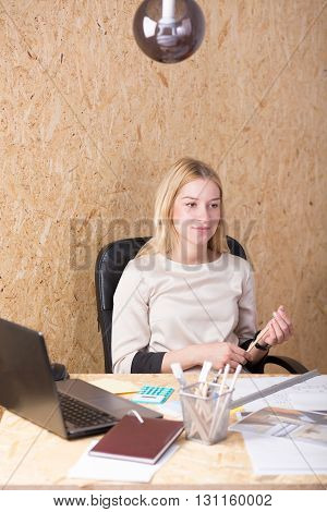 Smiling young architect in a chipboard-decorated office sitting behind a desk with laptop on it