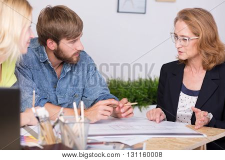 Middle-aged architect and a young man and woman sitting together at a drawing table and discussing plans of buildings
