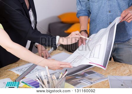 Close-up of a drawing table with papers and colour samplers on it and architects commenting on a technical drawing they are holding