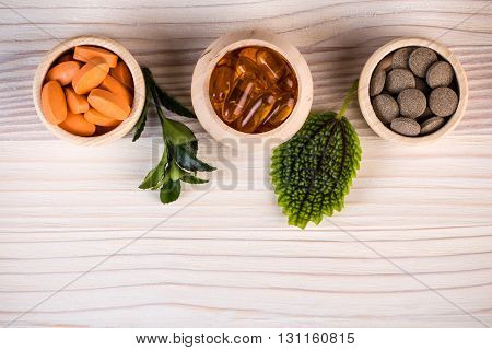 Various homeopathic pills in wooden containers and green leaves