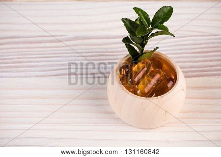 Homeopathic pills in wooden containers with green leaves hanging out
