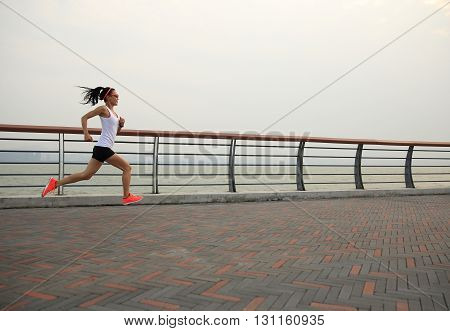 young fitness woman runner running on seaside