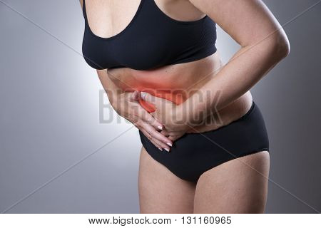 Woman with abdominal pain. Pain in the human body on a gray background with red dot