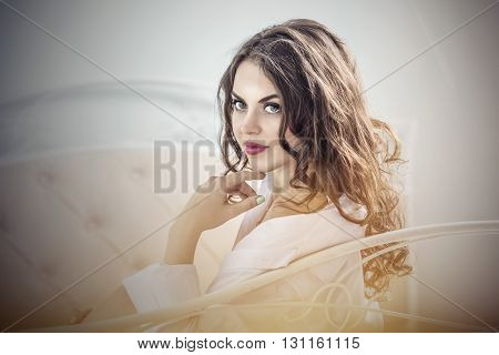 Beautiful woman in the morning sitting on the bed in a white shirt closeup