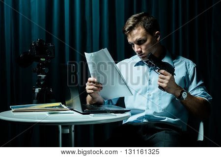 Man holding picture and gun sitting beside table in dark interior