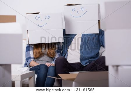 Shot of a young couple wearing boxes with happy faces drawings