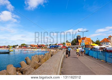 HEL, POLAND - AUGUST 10, 2015: People walking along the harbor waterfront with coastal protection structures made of concrete in Hel. Hel is one of most famous cruise travel destinations in Poland.