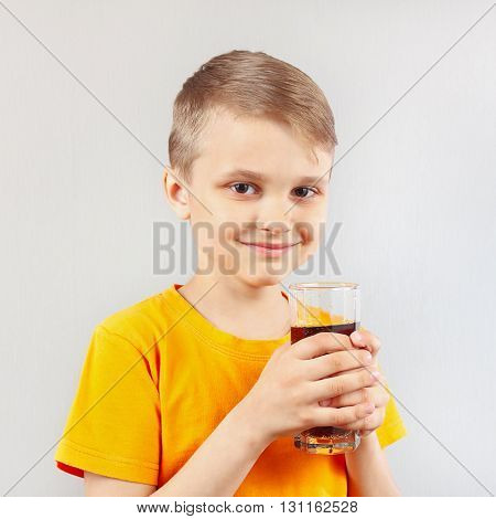 Little blonde boy with a glass of fresh cola