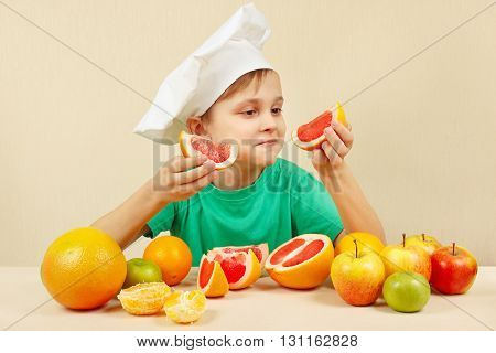 Young boy in chefs hat with two slices of grapefruit at the table with fruits