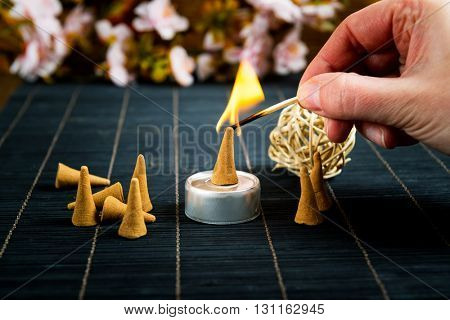 Traditional natural incense cones lighting with maches