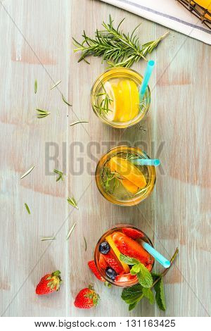 Top view of detox water cocktails on wooden table.
