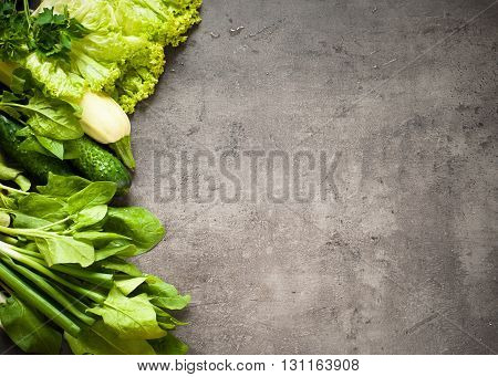 Green vegetables at slate background with space for text. Healthy eating and Diet concept. Vegan food background.