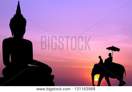 silhouette elephant with tourist in front of big buddha at sunset
