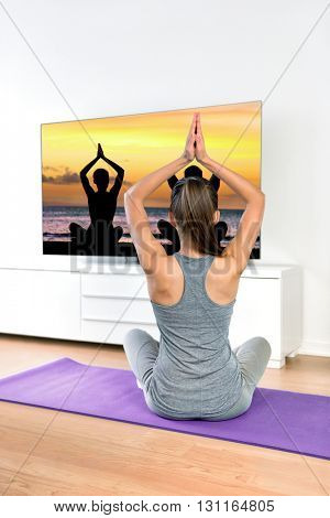 Woman watching TV yoga meditation fitness at home. Fit girl doing easy pose relaxation exercises following TV show online workout video with arms raised sitting on the floor of the living room.