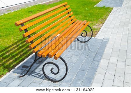 Empty Wooden Bench Stands On Cobblestone