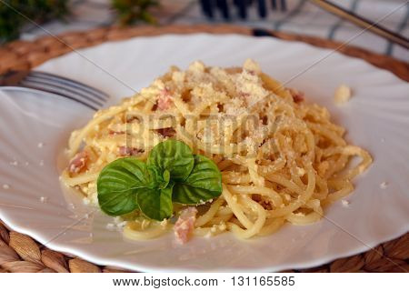 Italian spaghetti Carbonara on a white bowl on a table