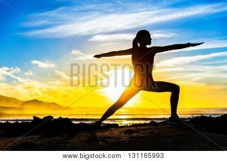 Silhouette of fitness athlete practicing warrior II yoga pose meditating at beach sunset. Woman stre