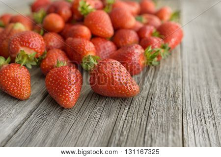 Ripe strawberries scattered on a wooden table.