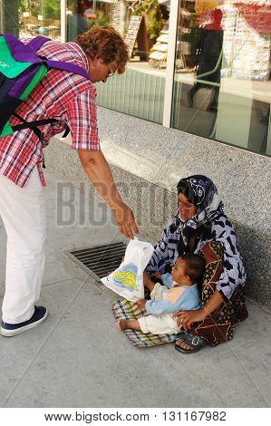 KUSADASI, TURKEY - JUNE 16, 2005: Woman gives to the beggar woman food for her baby