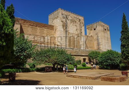 GRANADA, SPAIN - August 11, 2010: Tourists visiting Alhambra Granada Spain. Walls of Alcazaba fortress can be seen.
