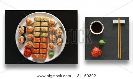 Japanese food restaurant, sushi maki gunkan roll plate or platter set. Set with chopsticks, ginger, soy sauce and wasabi. Sushi at black stone isolated at white background. Top view, Flat lay.