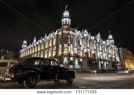 Havana, Cuba - June 23, 2015: A classic american car passing by the Gran Teatro in Old Havana, at night.