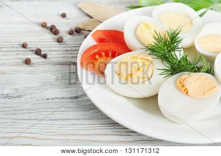 Boiled hen eggs in a white plate on a wooden background