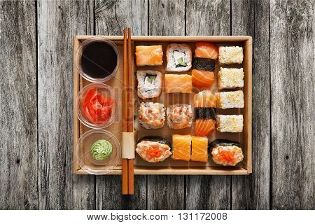 Japanese food restaurant, sushi maki gunkan roll plate or platter set. Chopsticks, ginger, soy sauce, wasabi. Sushi on rustic wood background, take away, delivery box. Top view.