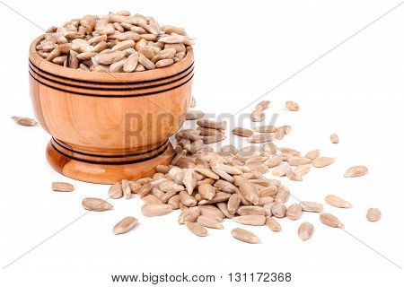 peeled sunflower seeds spill out of wooden barrels on a white background