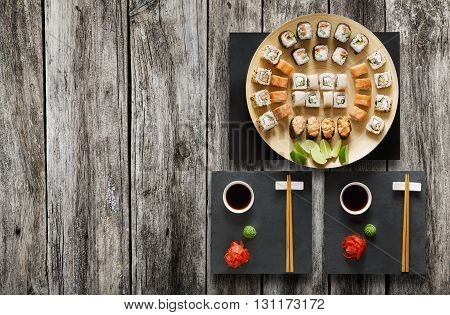Japanese food restaurant, salmon sushi maki gunkan roll plate or platter set. Chopsticks, ginger, soy, wasabi. Sushi at black stone mat and rustic wood background. Top view, flat lay, copyspace