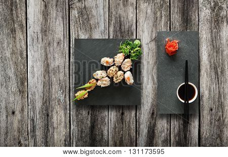 Japanese food restaurant, salmon sushi gunkan plate or platter set. Set for two with chopsticks, ginger, soy, wasabi. Sushi at black stone mat and rustic wood background. Top view, flat lay, copyspace
