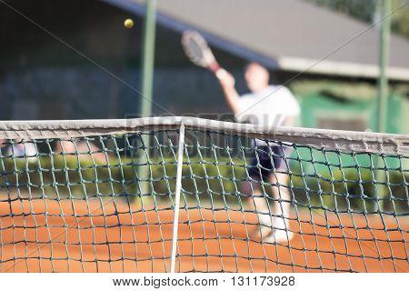 Tennis net Man plays tennis blurred motion