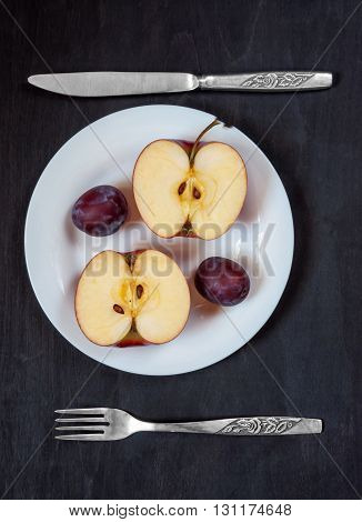 Apple and plum on a white plate with knife and fork on a dark background. Two halves of an apple on a white plate with knife and fork on a dark background. healthy Eating