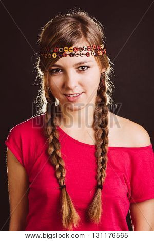 Beautiful blonde woman with braids and chic headband posing at studio - isolated on black.