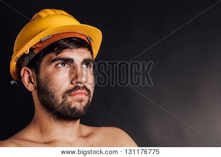 Portrait of an undressed bearded worker looking up - isolated on black.